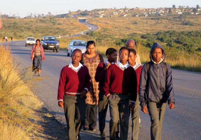 Mandira from the Grahamstown office walks with learners as they make their way to school. Thousands of learners walk far distances and for many hours in order to get an education.